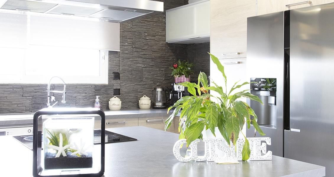 Cuisine moderne avec un îlot central et des pierres apparentes au mur
