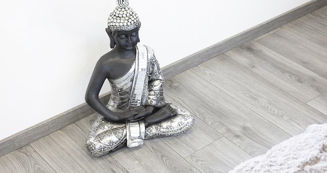 Statuette bouddha sur un sol en parquet