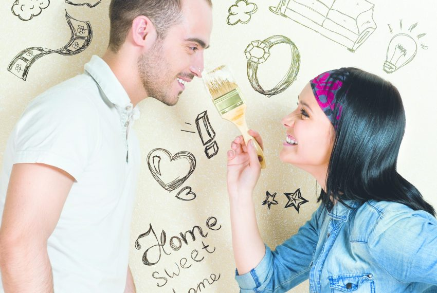 Couple peignant un mur de sa maison