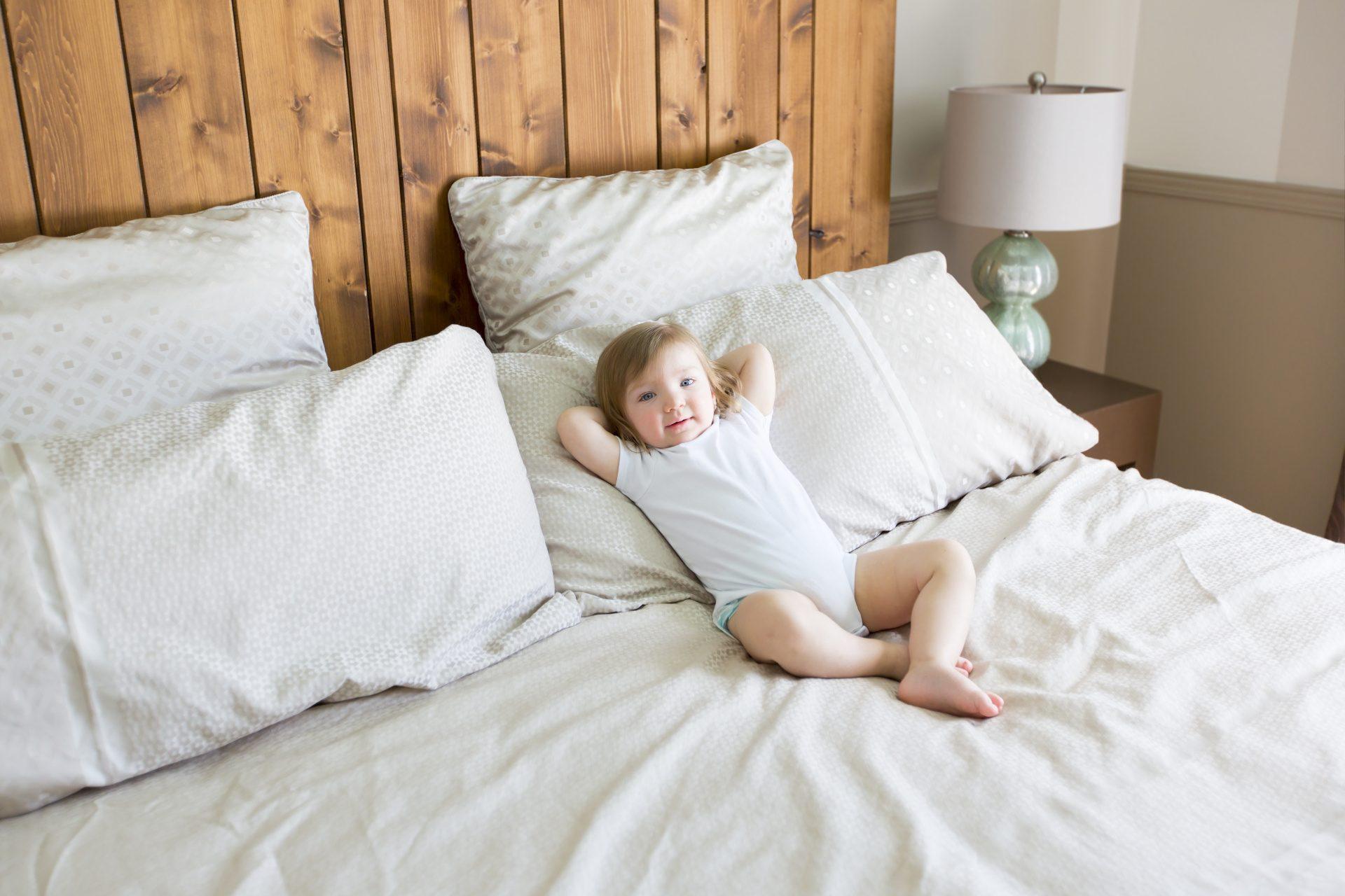 Mignon bébé tranquillement installé dans un grand lit