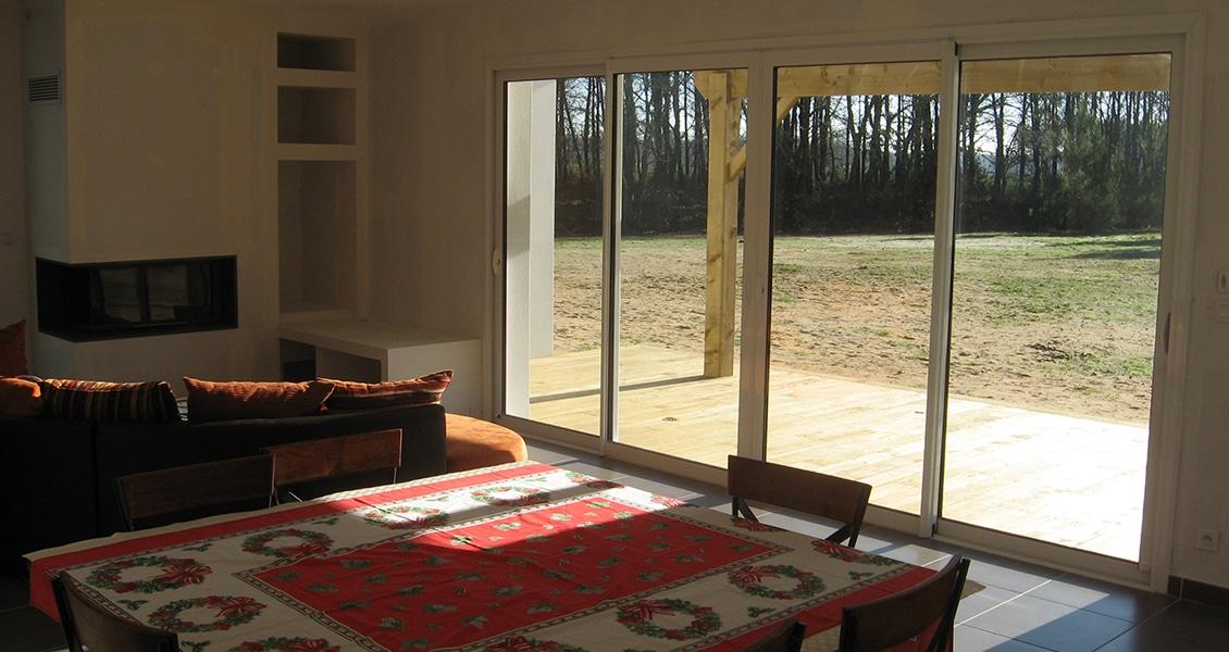 Salon d'une maison neuve avec coin cheminée et grande baie-vitrée 4 vantaux