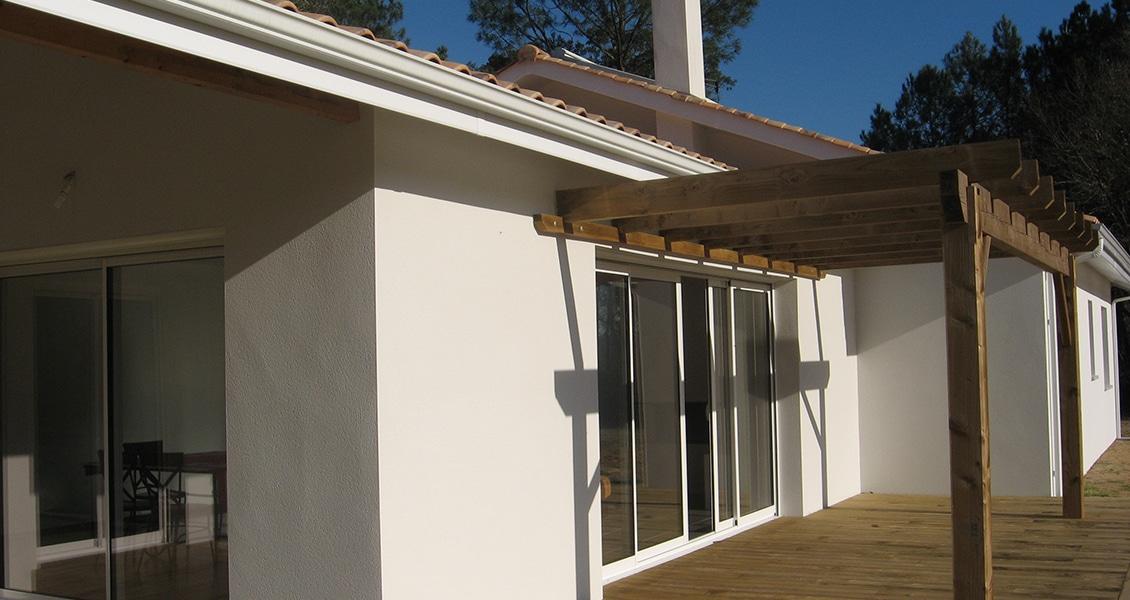 Pergola en bois d'une maison neuve devant une très grande baie vitrée 4 vantaux
