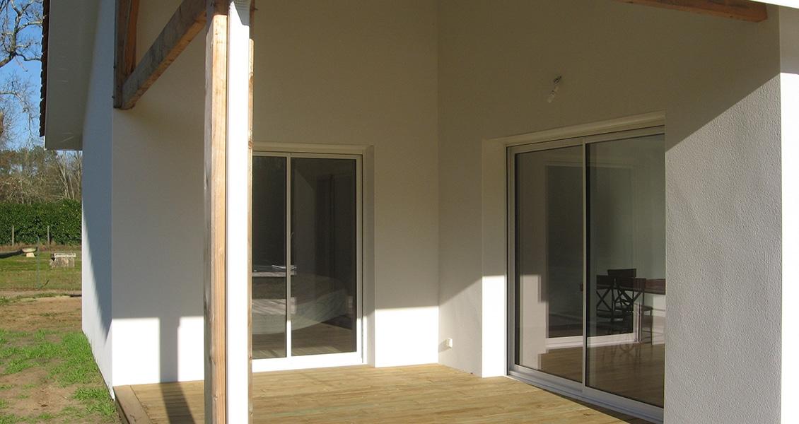 Deux baies-vitrées d'une maison neuve donnant accès à la terrasse couverte
