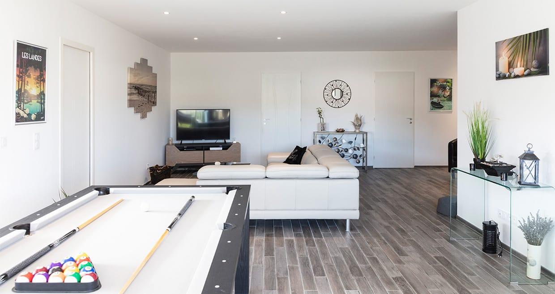 Espace de vie avec billard et canapé d'angle d'une maison moderne