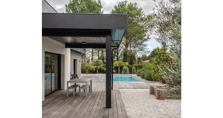 Terrasse couverte avec salon de jardin devant piscine