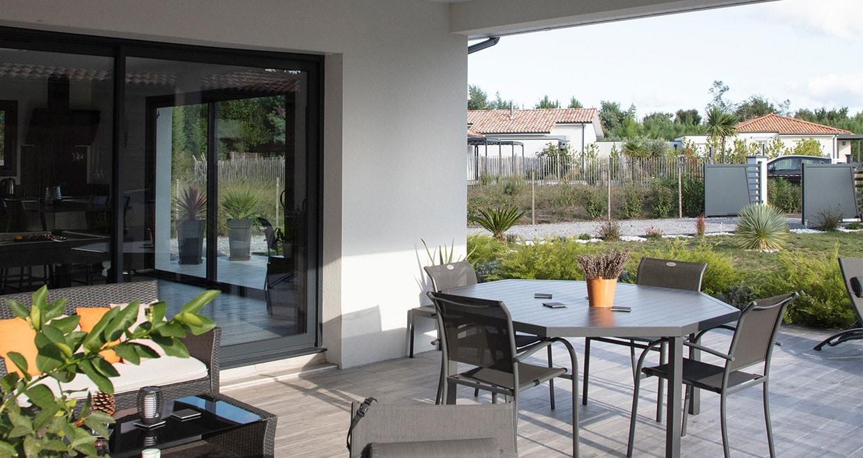 Terrasse couverte avec table extérieur et vue jardin