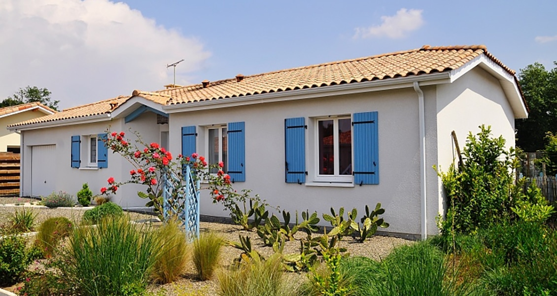 Maison landaise avec volets bleus et jardin arboré