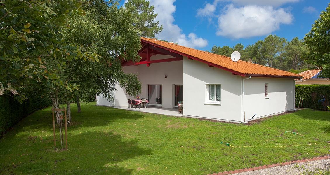 Jardin arboré d'une maison typiquement basque avec colombage rouge
