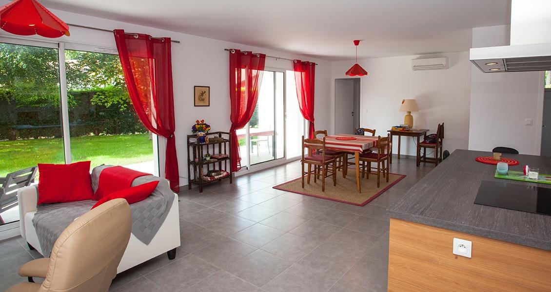 Salon-séjour lumineux avec deux baies-vitrées donnant sur le jardin
