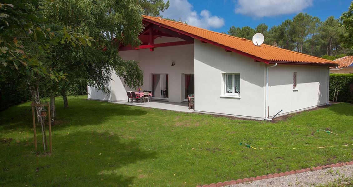 Terrase couverte d'une maison dans le Pays Basque avec joli jardin gazonné