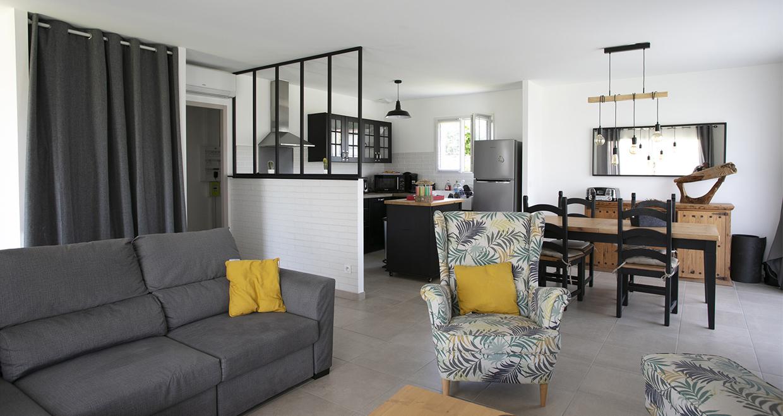 Salon et cuisine ouverte avec canapé et fauteuil