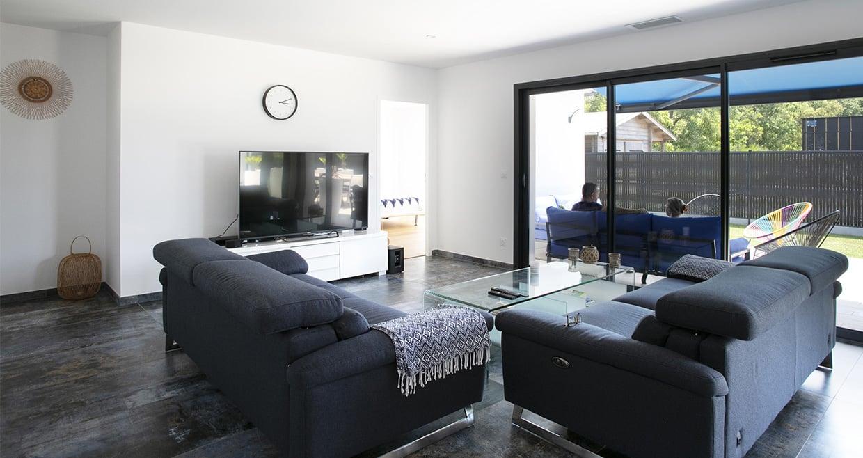 Grandes baies vitrées devant canapés et table basse
