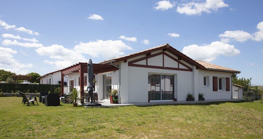 Maison moderne en forme de L avec colombage rouge et jardin engazonné