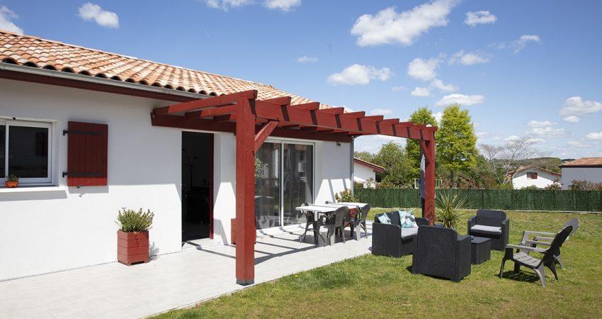 Jolie terrasse d'une maison au pays basque avec pergola en bois