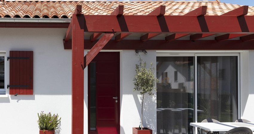 Pergola en bois de couleur rouge avec porte d'entrée rouge