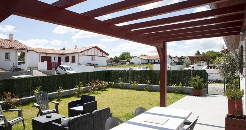 Terrasse d'une maison avec pergola en bois rouge