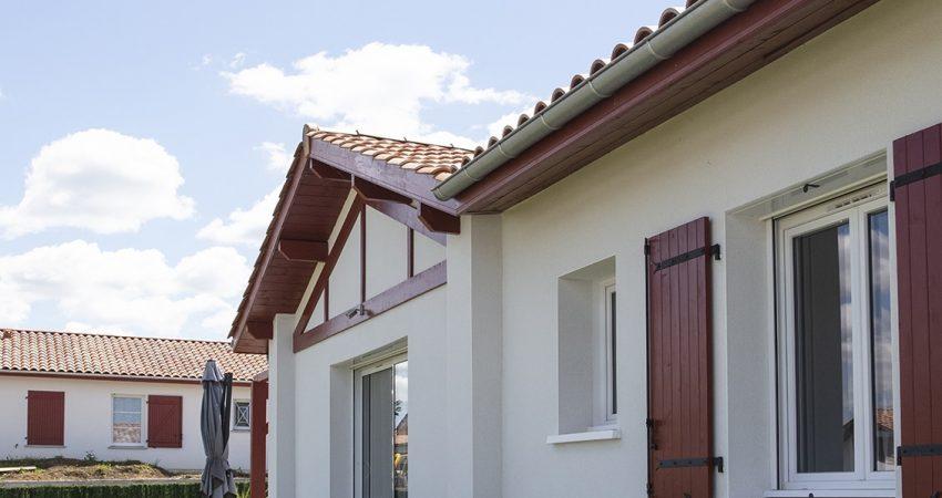 Maison basque avec façade claire et colombage rouge