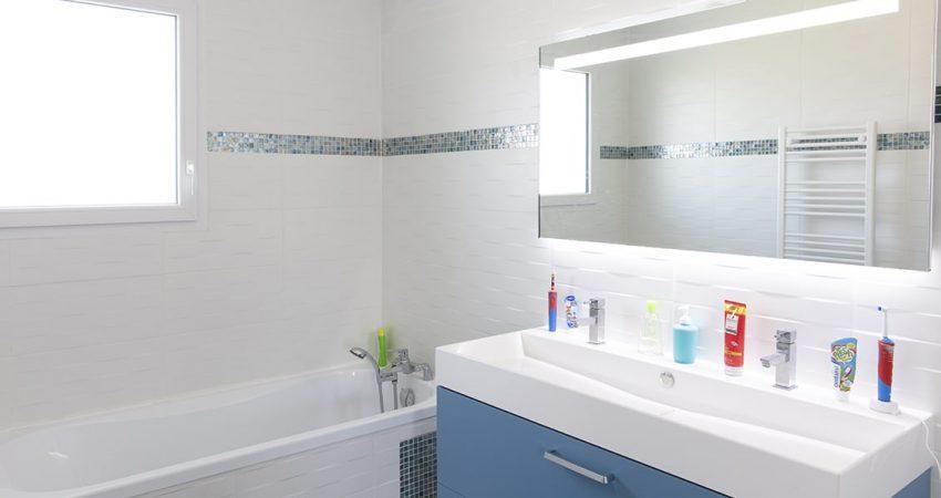 Salle de bain moderne avec baignoire et grand lavabo devant miroir rétroéclairé