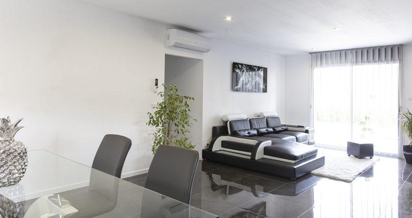 Salon d'une maison neuve avec un canapé et une méridienne devant la baie-vitére