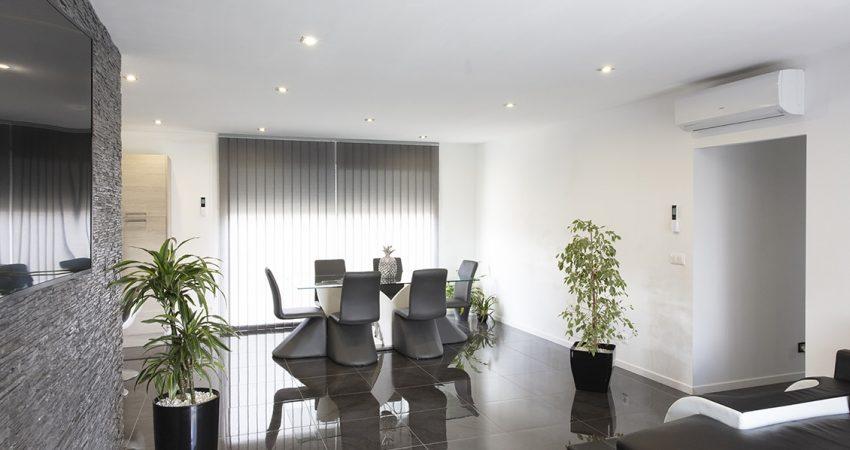 Vaste salon-séjour avec une grande table et une baie-vitrée qui illumine la pièce