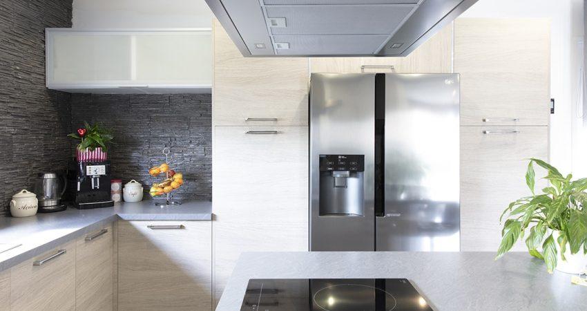 Une cuisine moderne avec un grand frigo américain intégré et un îlot central
