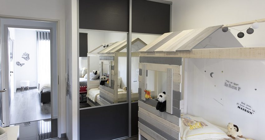 Chambre d'enfant avec un lit cabane et un grand placard
