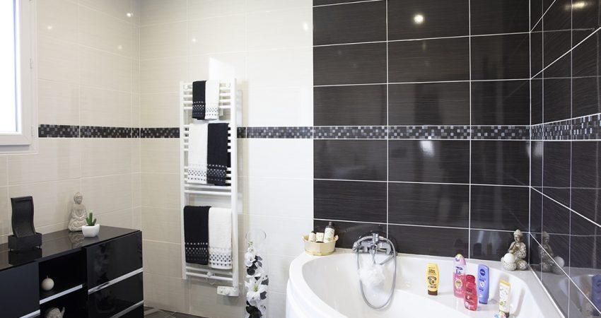 Belle salle de bain contemporaine avec baignoire d'angle et sèche serviettes