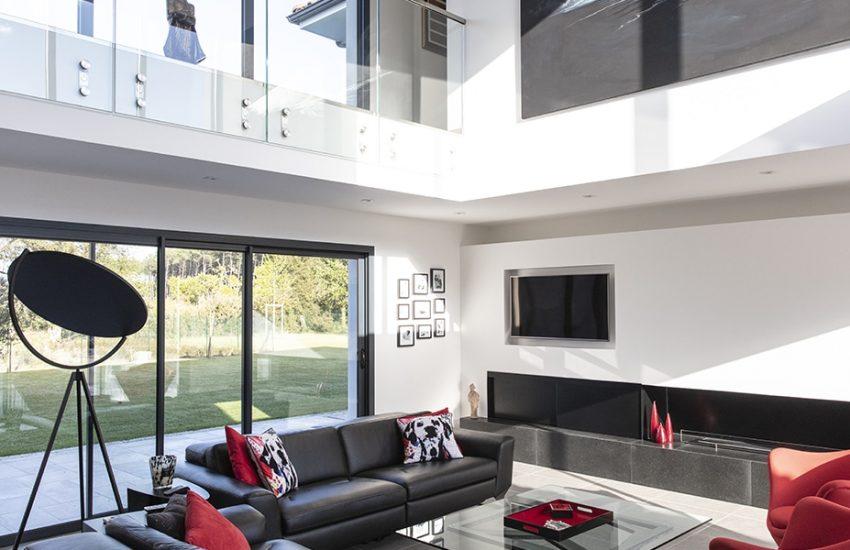 Salon baigné de lumière par un vide sous séjour et une immense baie-vitrée