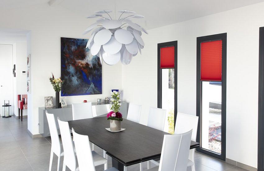 Salle à manger avec une table et ses fauteuils sous un lustre contemporain