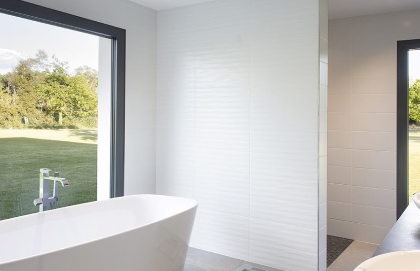 Salle de bain avec baignoire hors sol et ouverture vers le jardin