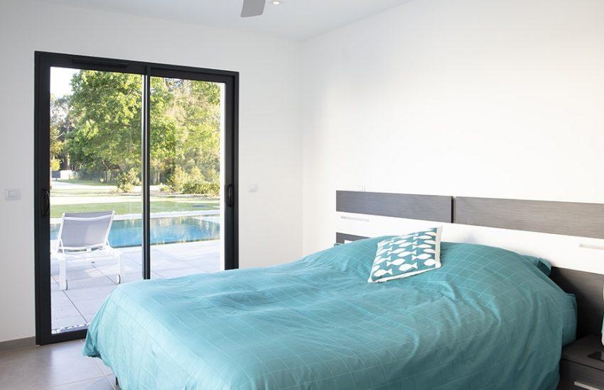 Chambre parentale avec baie-vitrée donnant sur la piscine