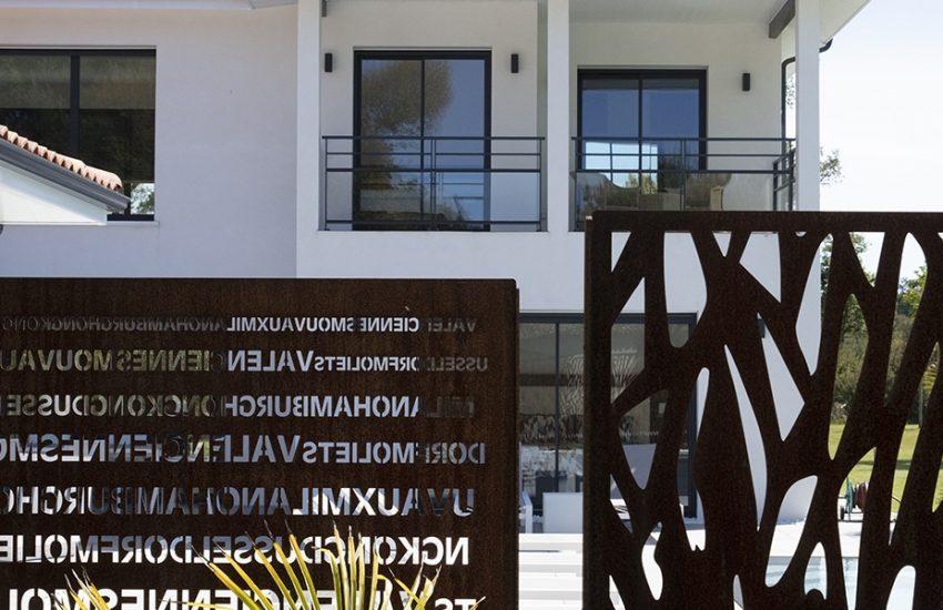 Brise-vue contemporain devant une piscine et une maison à étage moderne