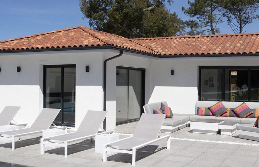 Extérieur d'une maison contemporaine avec une façade blanche et des menuiseries grises anthracites
