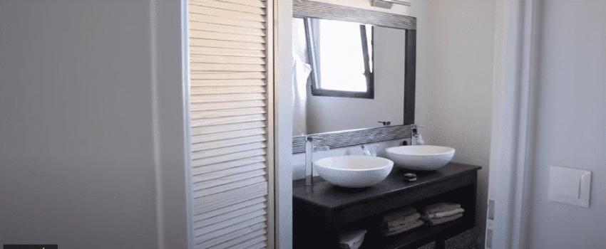 Salle de bain avec double vasque et grand miroir