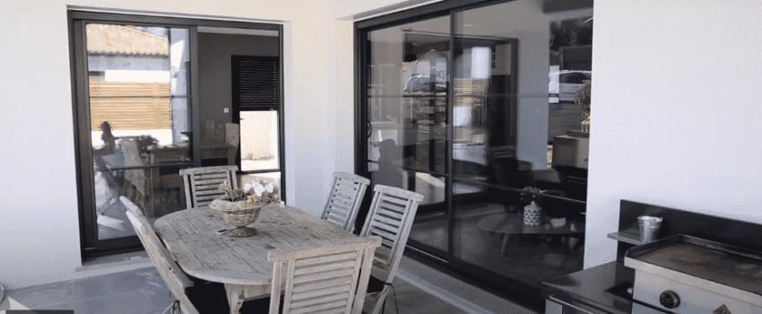 Terrasse extérieure couverte proche de grandes baies vitrées et avec table pour manger