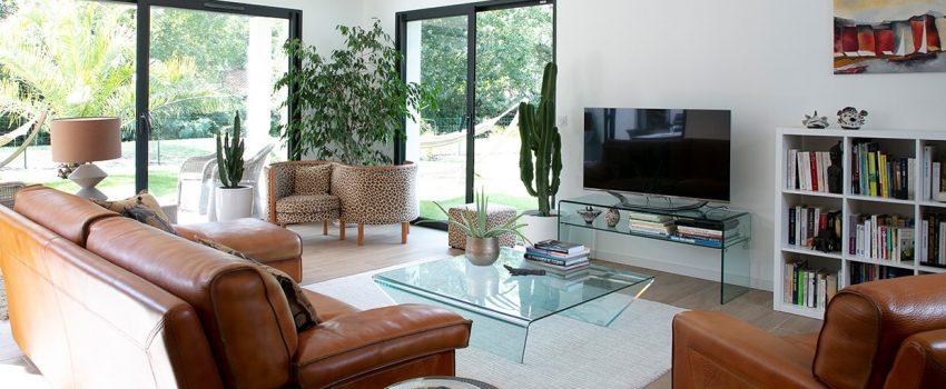 Coin TV d'un salon avec deux baies vitrées et bibliothèque