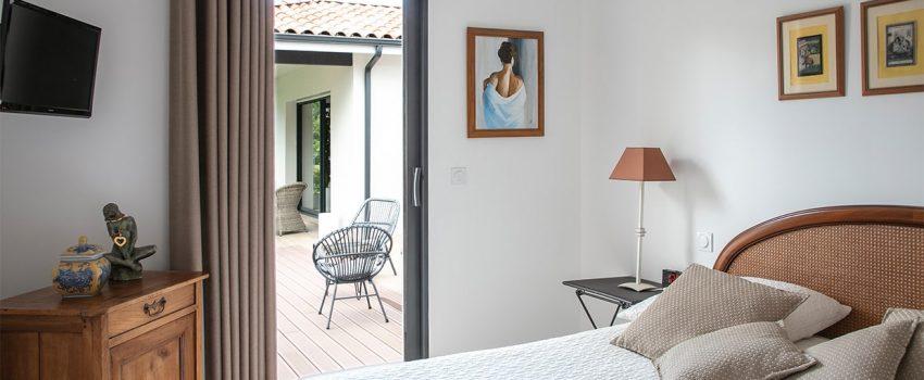 Chambre adulte avec porte fenêtre donnant sur terrasse