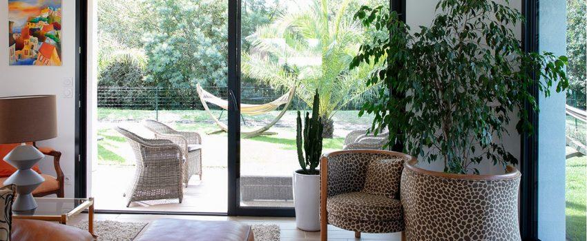 Salon avec grande baie vitrée donnant sur jardin