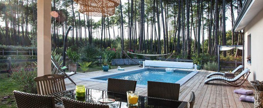 Terrasse couverte et piscine sous les pins