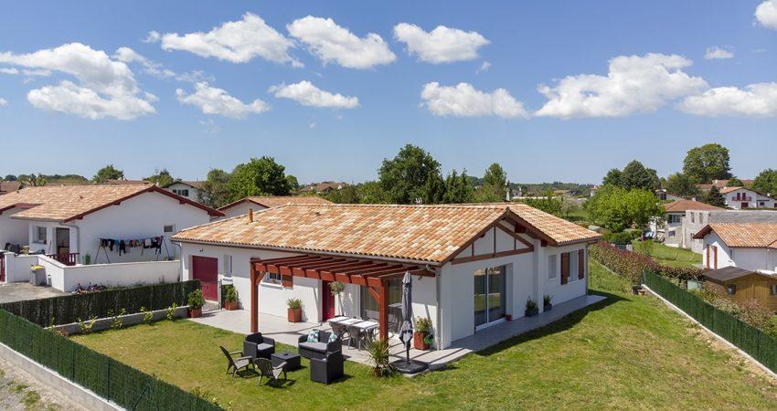 Vue aérienne d'une maison en L avec terrasse et jardin