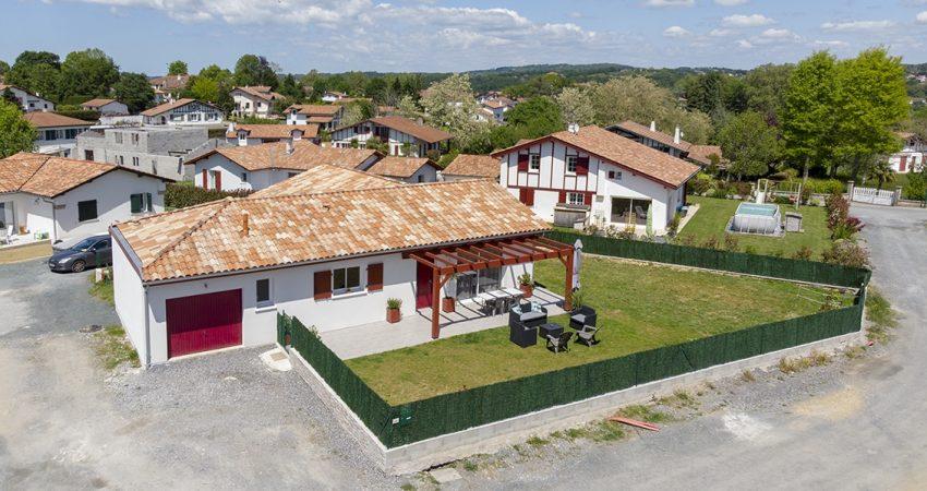 Maison en forme de L avec terrasse en bois et jardin arboré