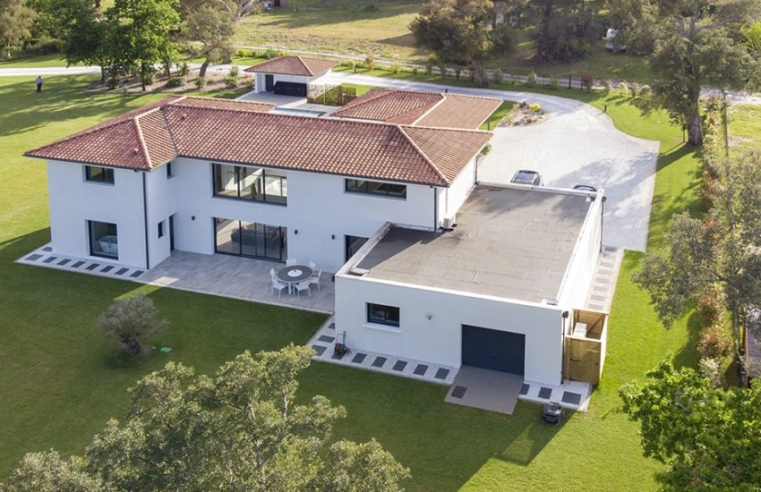 Maison contemporaine dans les Landes avec un jeu de toiture comprenant un toit 4 pans et un toit plat