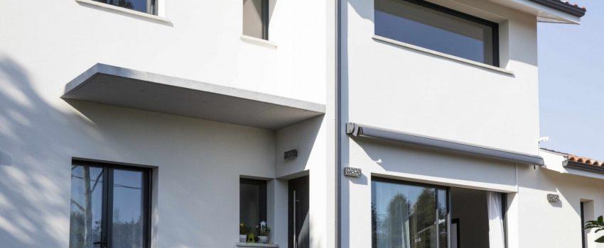 Maison moderne avec façade claire, menuiseries grises et casquette en béton