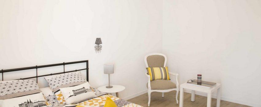 Chambre parentale avec coussins de couleurs et fauteuil Voltaire