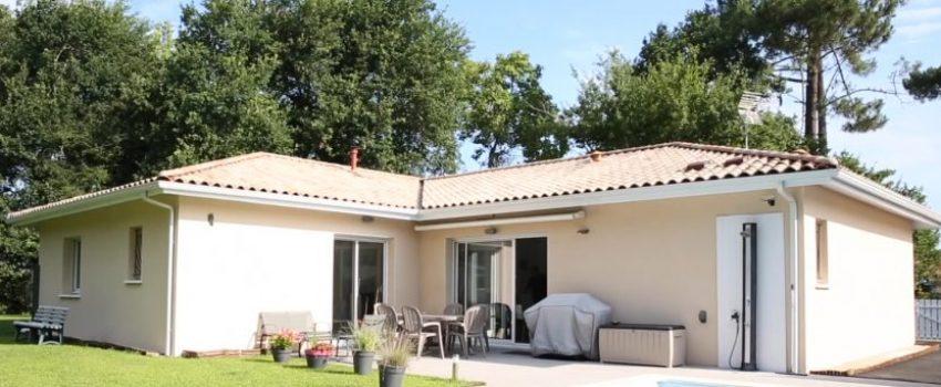 Maison en forme de L avec terrasse et douche d'extérieur