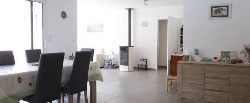 Salon et salle à manger d'une maison avec un poêle à granules