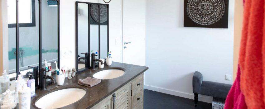 Une double vasque dans une salle de bain au style industriel avec miroirs en métal