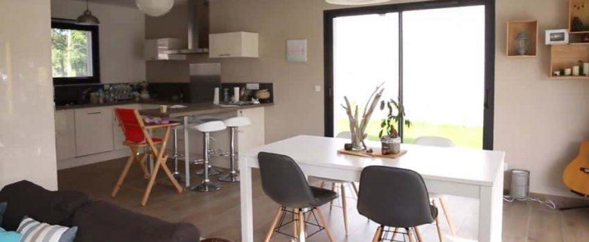 Une cuisine ouverte sur salle à manger et salon avec de grandes baies vitrées.