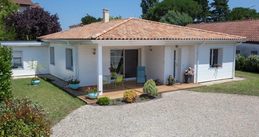 Maison neuve avec terrasse en bois et allée gravillonée