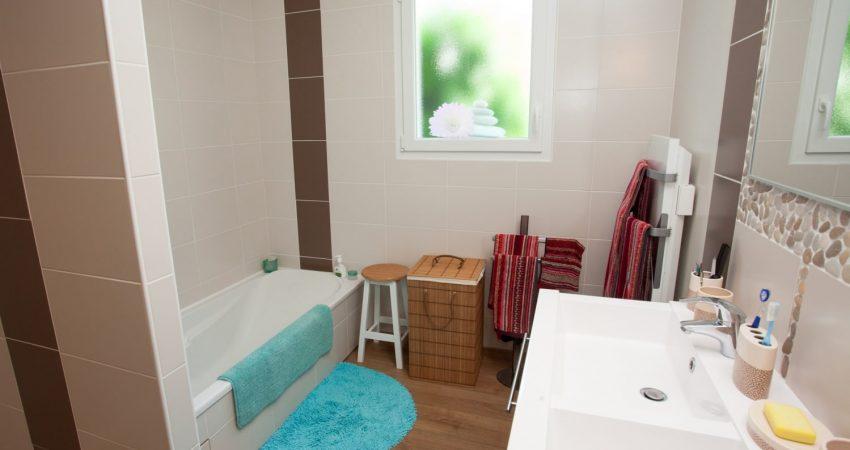 Salle de bain avec baignoire, meuble double vasque et sèche serviette moderne